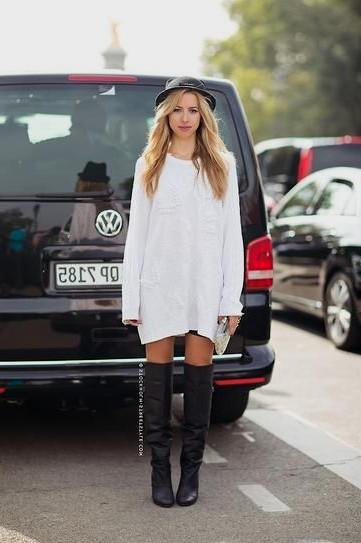 white long-sleeved dress with black felt hat and leather boots