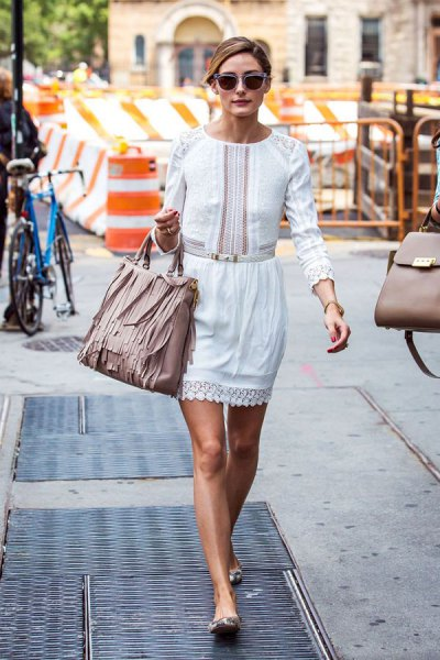 white long-sleeved mini dress with a ruffled waist and light pink leather wallet with fringes