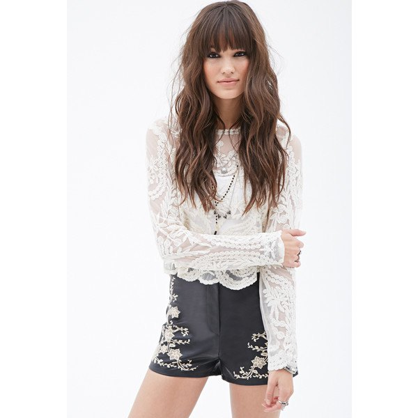 white long-sleeved lace top with black shorts embroidered with leather
