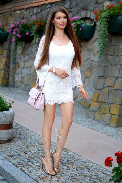 white long-sleeved mini dress with gold gladiator sandals