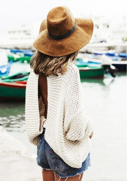 white, oversized long-sleeved sweater with blue denim shorts and floppy hat