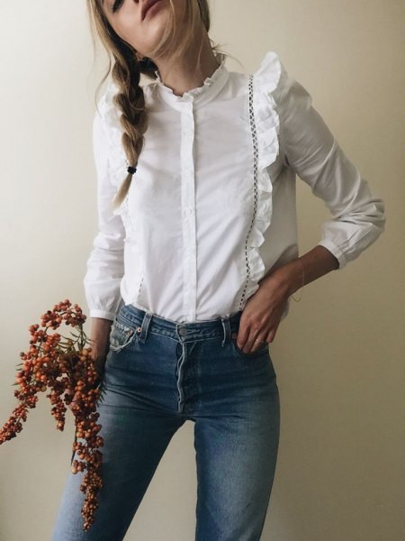 white long-sleeved shirt with ruffled buttons and blue skinny jeans