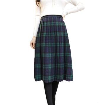white long-sleeved sweater with green and dark blue midi plaid skirt