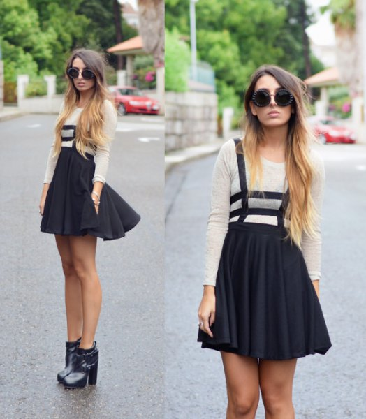 white long-sleeved T-shirt with black mini pleated skirt and boots with ankle heel