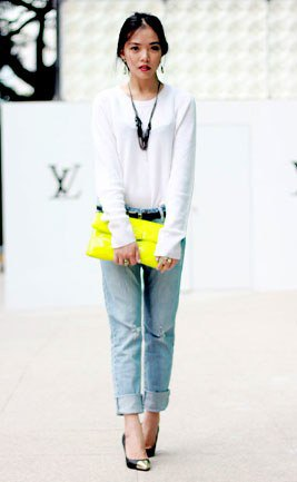 white long-sleeved T-shirt with light blue jeans with cuffs and yellow clutch