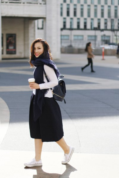 white long-sleeved top with black flared midi skirt and backpack wallet