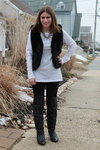 white long-sleeved tunic top with black jeans and knee-high leather boots
