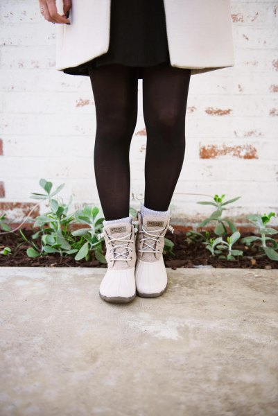 white long wool coat with black stockings and white duck boots