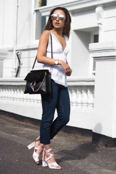 white sleeveless top with a low cut and open toe heels made of silver velvet
