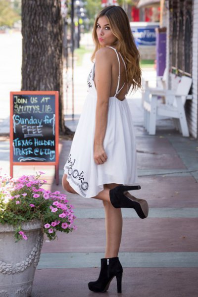 white midi babydoll dress with open back and black suede boots