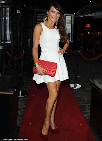 white mini skater armored dress with red leather clutch