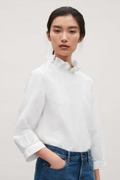white mock-neck blouse with blue skinny jeans
