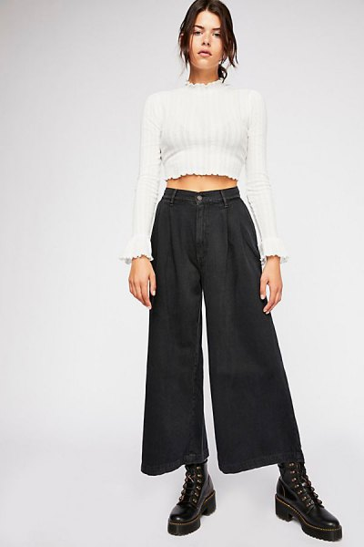 white, short cut sweater with mock neck and black pleated jeans