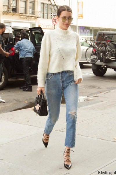 white ribbed knit sweater with stand-up collar and ripped knee jeans