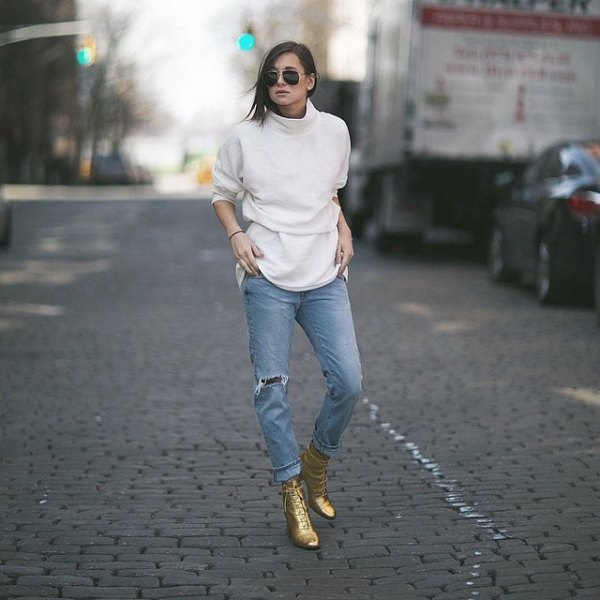 white mock-neck sweater with light blue boyfriend jeans and gold combat boots