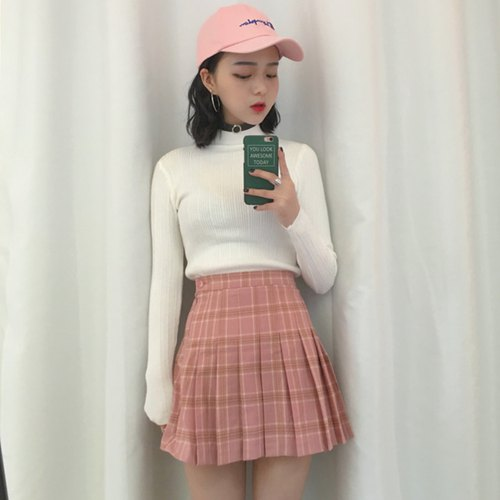 white mock-neck sweater with pink, high-waisted pleated mini skirt