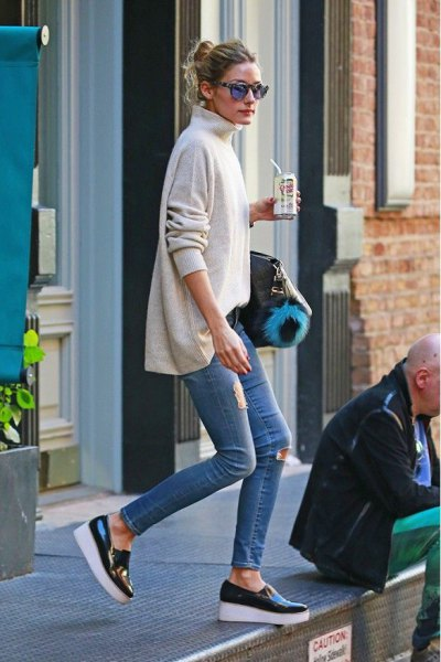 white mock-neck sweater with skinny jeans and black sneakers made of wedge leather