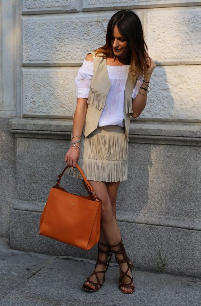 White off-the-shoulder blouse with a crepe fringed vest and an orange handbag