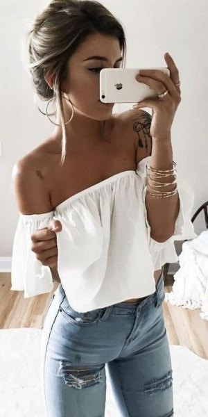Off-the-shoulder evening top in white with light blue skinny jeans