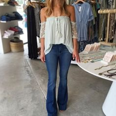 white blouse pleated off the shoulder with flared blue jeans