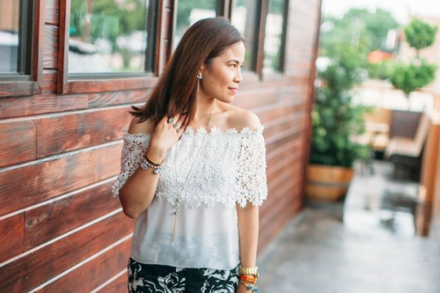 Off-the-shoulder, semi-transparent top made of lace and chiffon with a black skirt with a floral pattern