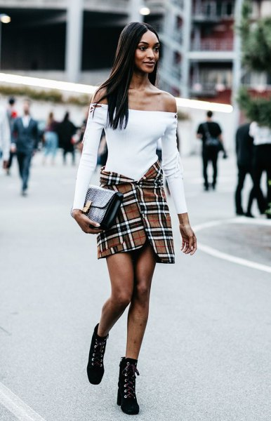 Off-the-shoulder white sweater with a red and black checked wrap skirt