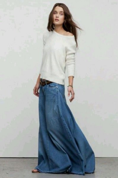 white sweater with one shoulder and a loose fit and floor-length denim skirt