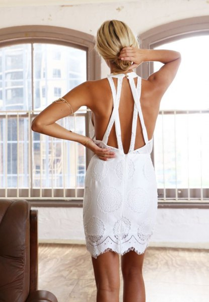 white mini crochet dress with an open back and a straight cut