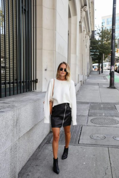 white oversized knitted sweater with black mini leather zip skirt