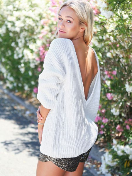white oversized sweater with deep V-neck and open back and silver shorts