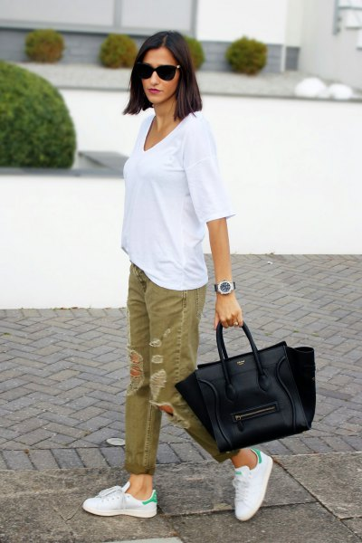 white oversized t-shirt with green ripped khaki jeans
