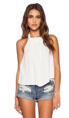 white, flowing tank top with pleats and denim shorts