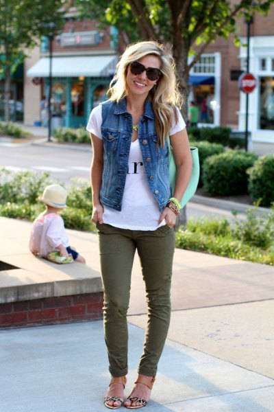 white printed T-shirt with denim vest and green skinny jeans