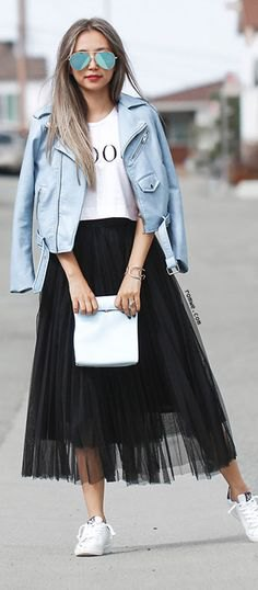 white printed T-shirt with blue-green leather jacket and black mesh skirt