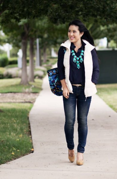 white puffer vest with shirt with buttons and dark blue skinny jeans