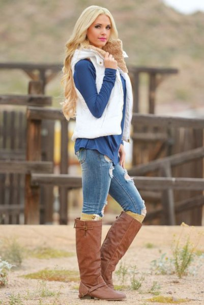 white puffer vest with a dark blue blouse and brown knee-high boots