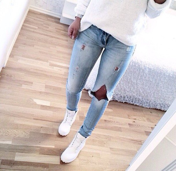 white knitted sweater with a loose fit, light blue jeans and boots