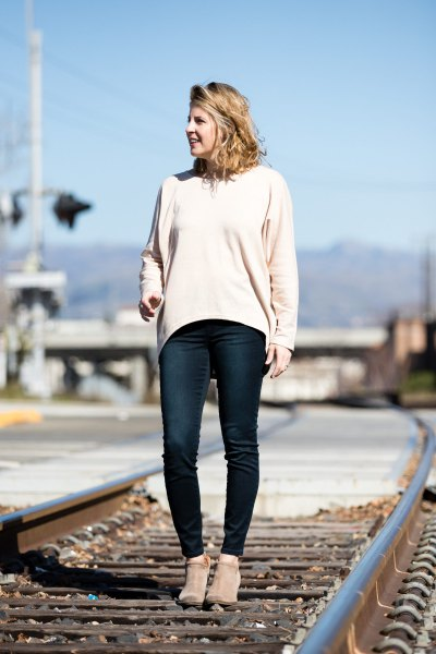 white sweater with a relaxed fit and dark blue skinny jeans