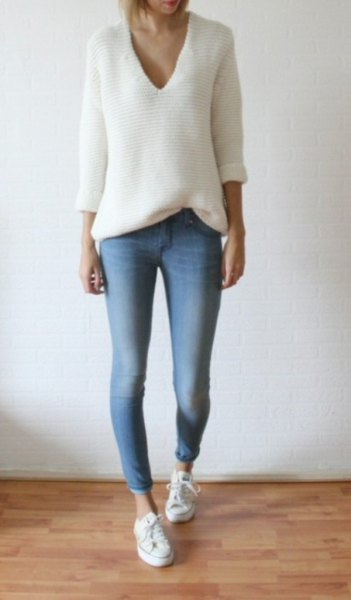white knitted sweater with relaxed fit and V-neckline and light blue skinny jeans