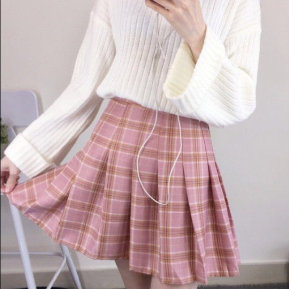 white ribbed knitted sweater with a red, pleated, checked mini skirt