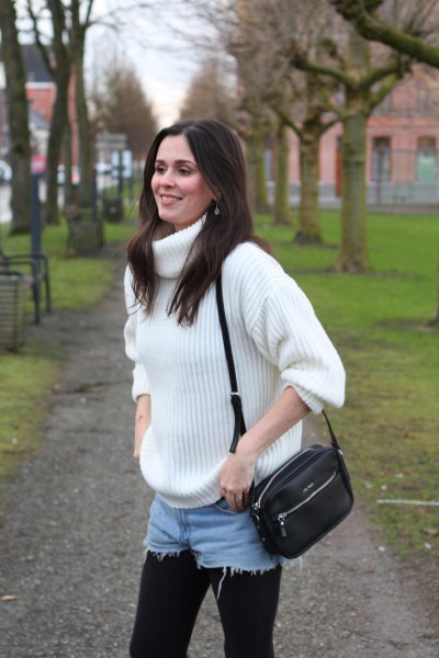 white, thickly ribbed turtleneck with blue denim shorts and leggings