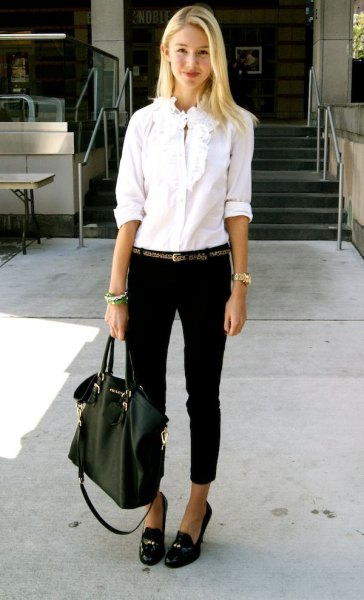 white shirt with ruffled buttons, black jeans with cuffs and slippers with tassels