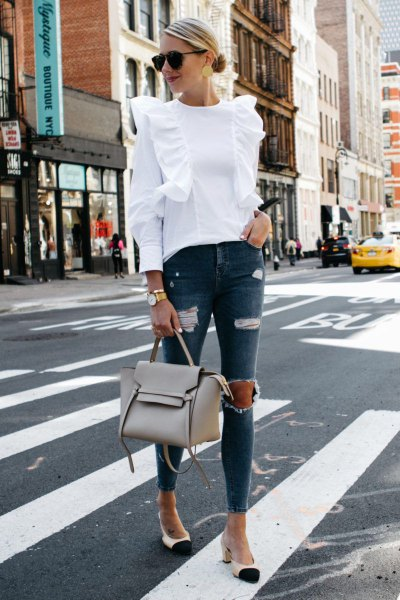 white ruffled shoulder blouse with ripped gray skinny jeans