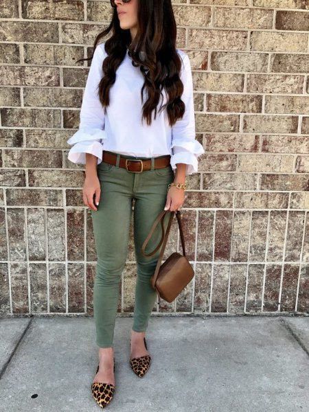 white blouse with ruffle sleeves and olive-colored skinny jeans