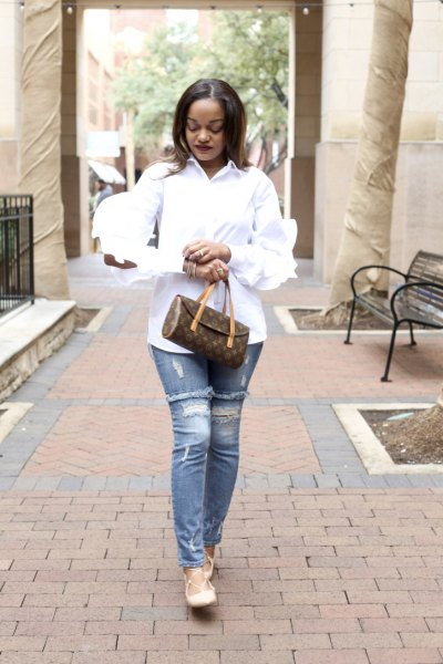 white shirt with ruffled sleeves and buttons with ripped, narrow-cut jeans
