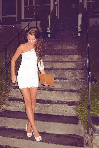 white figure-hugging mini dress with scalloped edge and red clutch