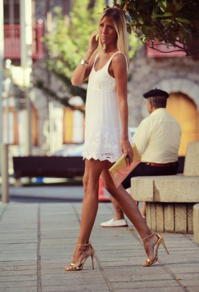 white lace dress with scalloped hem and golden high heels with open toes