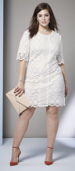 white lace dress with scalloped hem and red heels with ankle straps