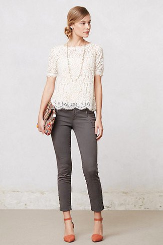 white short-sleeved lace blouse with scalloped hem and gray skinny jeans with ankles