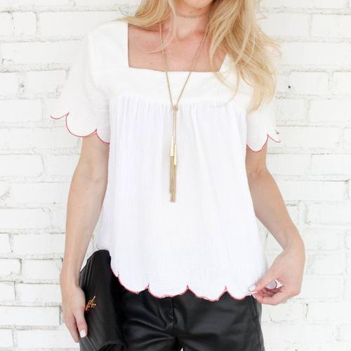 white square blouse with scalloped hem and black silk trousers